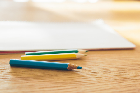 Color pencils and white notebook on a wooden table with selective focus.