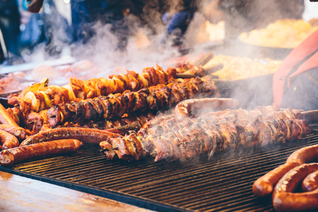 Meat skewers and sausages barbecued on a grill at  Krakows Christmas market.