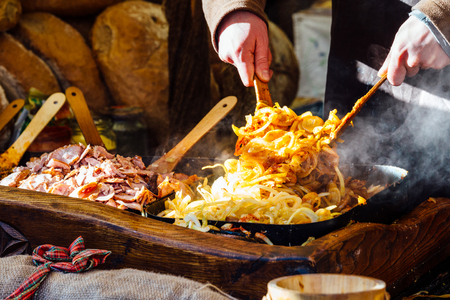 Krakow Christmas market stall serving traditional slices of bread with grilled meat, onions and sauce.