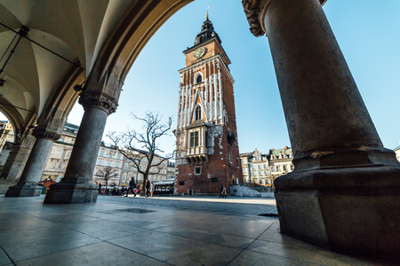 Krakow, Poland - December 30, 2017: Wide angle view of the Town Hall Tower, seen through the columns of the Cloth Hall located on the main market square in the old town of Krakow.