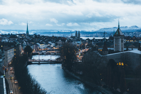 Aerial view of Zurich city center at dawn, with the Limmat river in the foreground and the old town in the background.