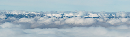 The Jura mountain emerging from the winter fog. Stock Photo