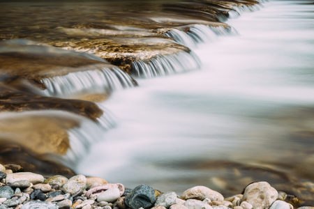 Small waterfall in a riveer with blurred water flow from long exposure.