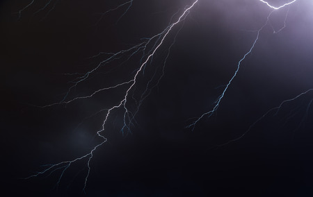 Night sky illuminated by lightning bolts