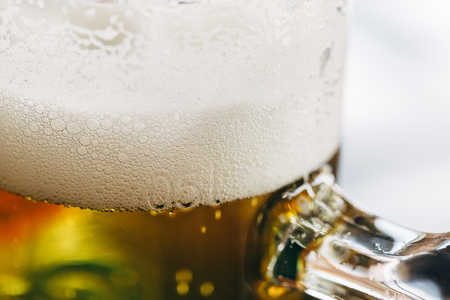 Close up of a half-liter glass of beer with frothy foam on top.