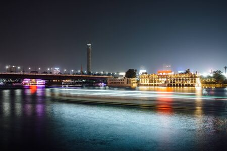 Cairo city center at night, long exposure with light trails of moving boats on the Nile river. Stock Photo