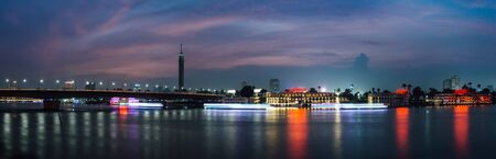 Panoramic of Cairo city center at night, long exposure with light trails of moving boats on the Nile river.
