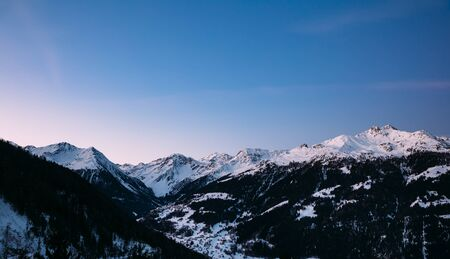 Morning sky over snowy mountains at sunrise in the Swiss Alps.