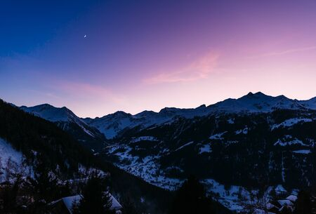 Purple and blue sky over snowy mountains during sunset in the Swiss Alps.
