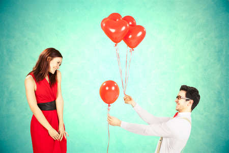courtship: Man approaching woman giving her red heart shape balloons with light blue background