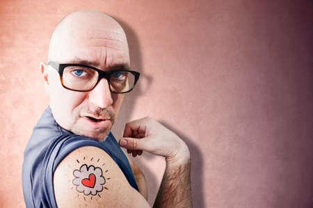 Divertido Latin Lover muestra su tatuaje, fondo de color rosa
