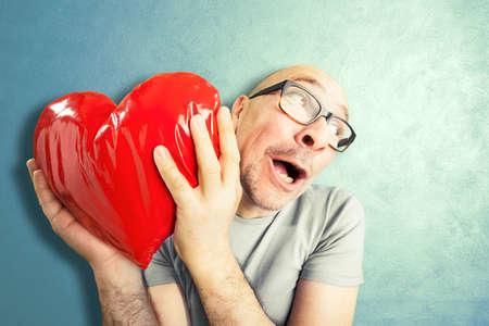 El hombre en el amor tiene una forma de corazón rojo almohada