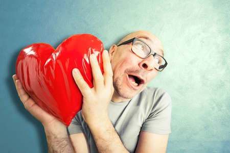distorted image: Man in love holds a red heart shape pillow Stock Photo