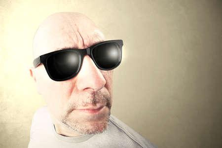 hombre con gafas de sol negras buscando foward, fondo beige Foto de archivo