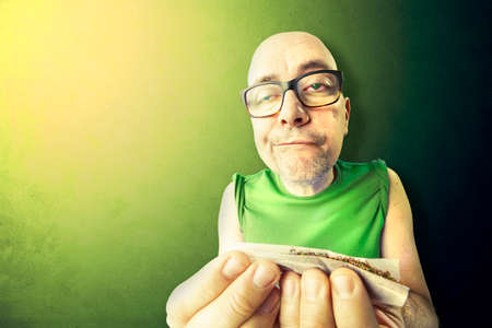 junky: tossic and relaxed man rolling herb and tobacco Stock Photo