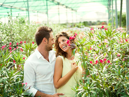 couple have fun choosing flower pots in a greenhouse photo
