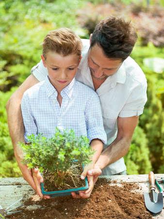 父親が植物の世話をする息子を教育します。