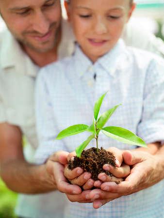 educacion ambiental: Padre educar hijo a cuidar una planta