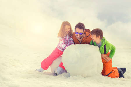 large family: father and his son and doughter building a snowman, snow