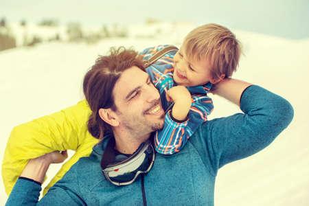 父の優しさで雪の中で愛情を込めて彼の息子を持ち上げる
