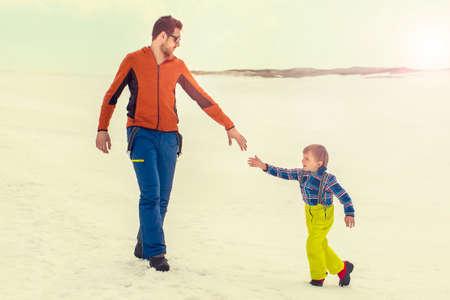 父は彼に彼の手は、雪を与える彼の若い息子を助ける 写真素材