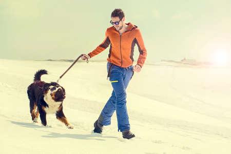 男と彼の犬は、夕暮れ時の雪の中で実行