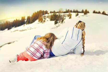母と娘のサンセットを見て雪の上で休憩
