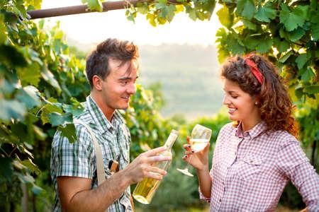 農業の収穫の後にワインを飲むカップル