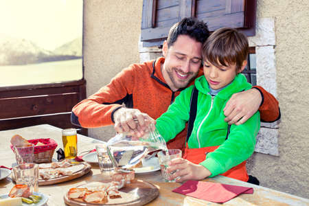 family eating: father and son having lunch in a chalet in the mountain Stock Photo