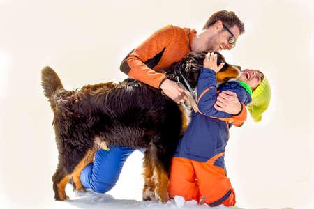 父、息子および彼らの犬は雪の中で楽しい時を過す
