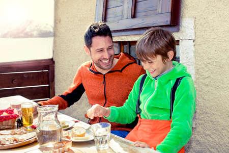 父と息子は山のシャレーで昼食をとった