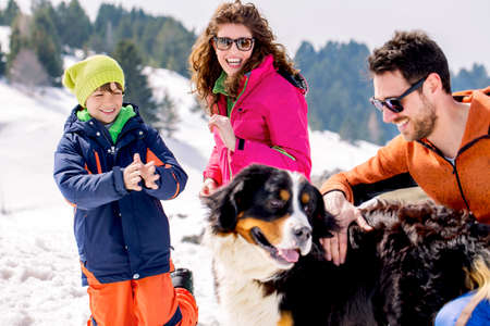 a big family: family with dog having fun in the snow Stock Photo