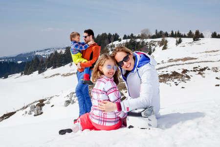 雪の中で楽しさを持っている家族