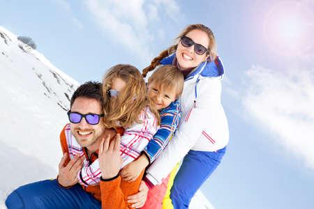 雪の中で楽しんで若い家族 写真素材