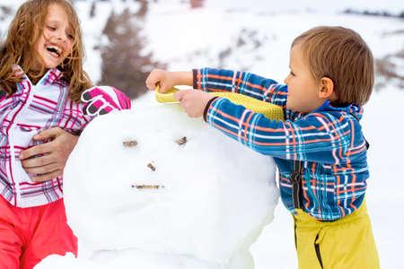 兄と妹は雪だるまを構築 写真素材