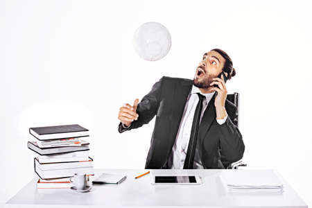 Surprised business man hitting the ball with head