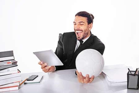 仕事をしながらサッカーの試合に関するビジネス男ベット 写真素材