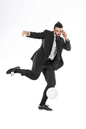通話しながらボールを蹴るビジネス男