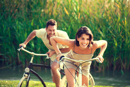 overcome a challenge: Couple having a bicycles race into the nature
