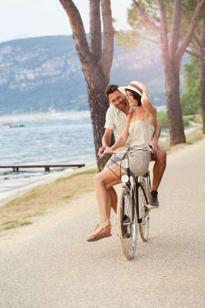 湖水地帯の自転車に彼の女性を運ぶ男 写真素材