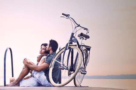 自転車で湖の遊歩道沿いに休息の愛のカップル
