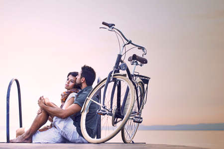 Couple in love resting on a boardwalk with a bike at the lake photo