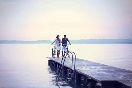 湖の遊歩道を自転車を押して愛のカップル