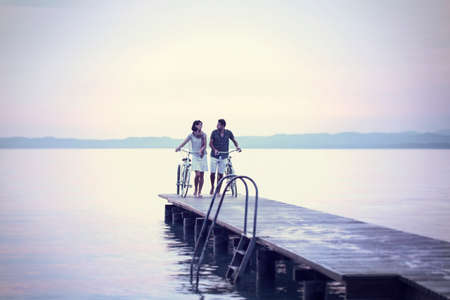 primacy: couple in love pushing bike on a boardwalk at the lake