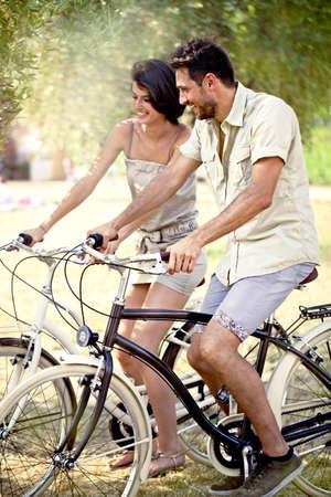 イタリアの湖の休日自転車で楽しみを持っているカップル 写真素材