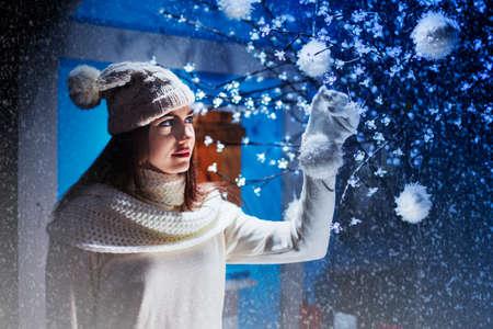女の子がクリスマス ツリーに飾りを置く