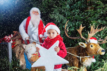 Santa Claus with his little helper and his reindeer photo