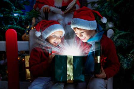 クリスマスのギフトを開く 2 人の子供 写真素材