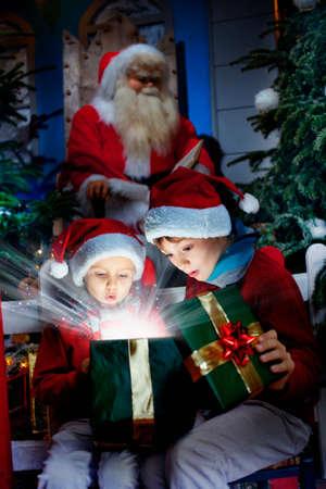 驚いた子供たちは光のクリスマス ギフトの光線を魔法を開く 写真素材