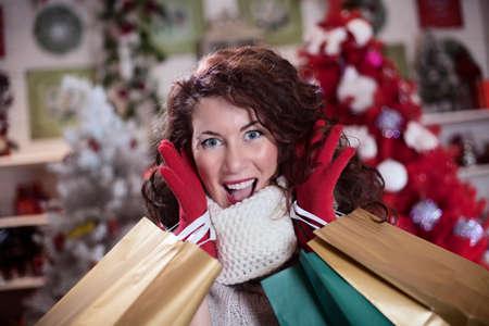 彼女の買い物袋を持つ美しい女性は、カメラを見て興奮してください。
